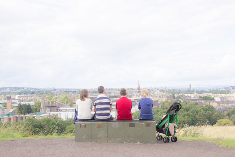 Rear View Of Family Sitting On Bench Against Sky