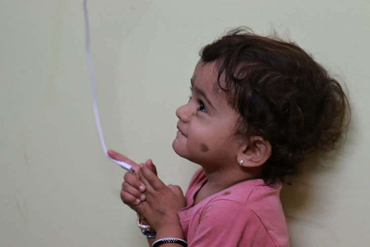 Cute girl with cable standing against wall