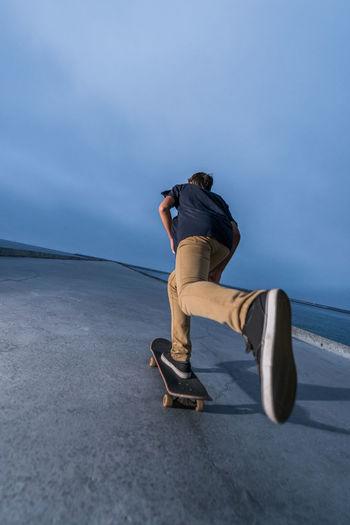 Rear view of man skateboarding on sea against sky