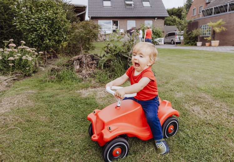Smiling baby girl sitting on toy car at yard