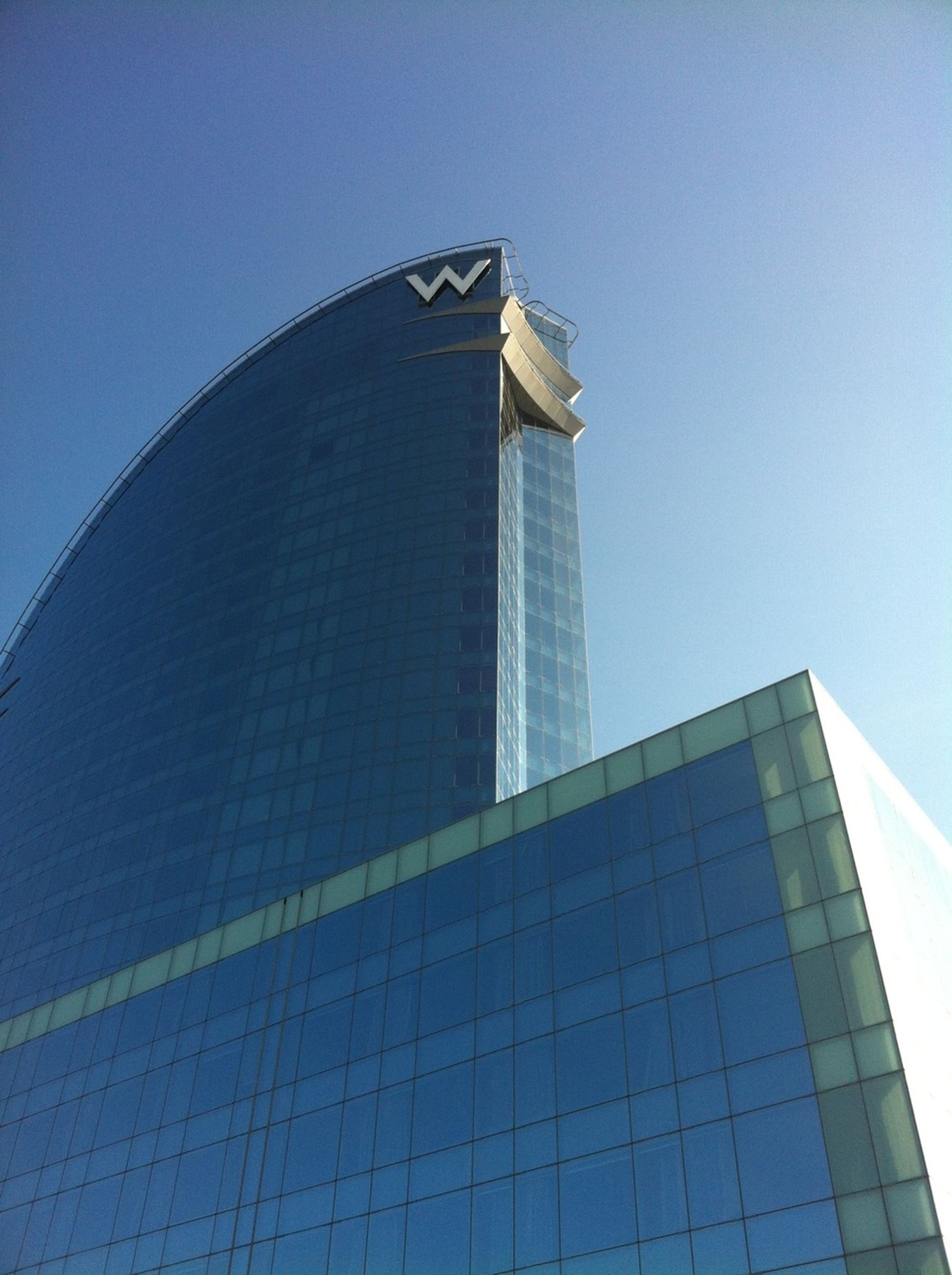 architecture, built structure, building exterior, low angle view, clear sky, modern, blue, city, tower, office building, tall - high, skyscraper, glass - material, reflection, famous place, capital cities, building, day, sky, travel destinations