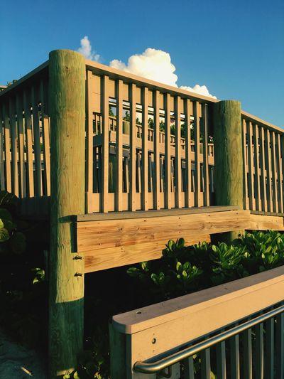 Wooden boardwalk at beach against sky
