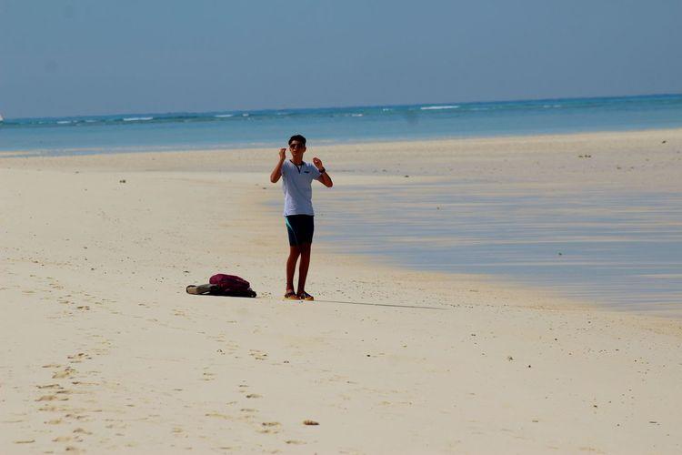 Full Length Of Teenage Boy At Beach Against Sky