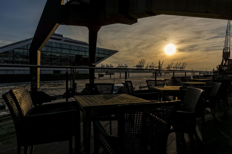late afternoon sun Afternoon Backlight Dockland Elberadweg Hamburg Harbour Modern Architecture Nikon Tables And Chairs Cafe Chair Clouds And Sky Container Bridges Cranes Of Hamburg Day Empty Frozen River, River, Sky, Snow, Snow Covered Trees, Sun Shine, Tree, Trees, Winter March Nature Nikonphotography No People Outdoor Cafe Outdoors Restaurant Riverbank Sea Sky Sun Sunset Table Under The Crane Water ıce