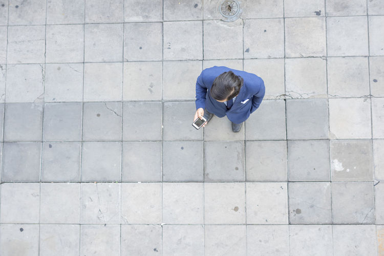 Directly Above Shot Of Young Businessman Using Phone On Footpath