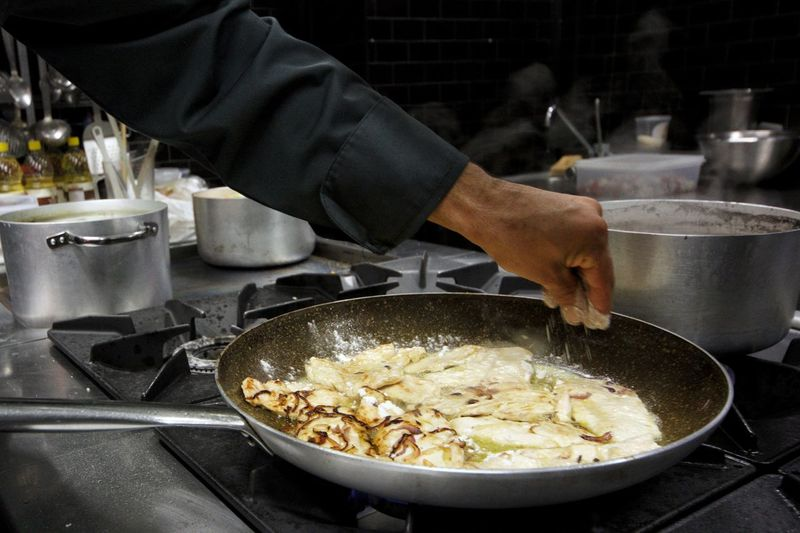 Midsection of chef preparing food in kitchen at restaurant