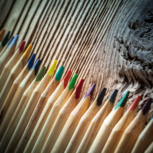 Close-up of multi colored pencils on wood