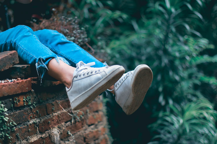 Low section of boy sitting on brick wall