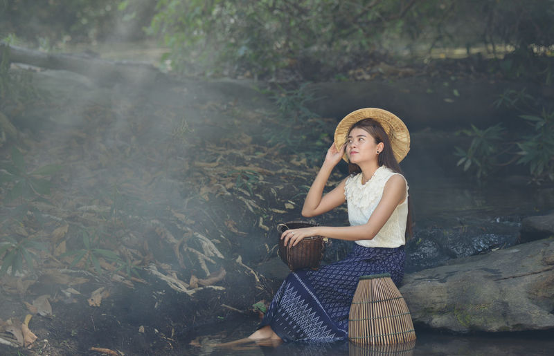 Young Woman Wearing Straw Hat In Forest