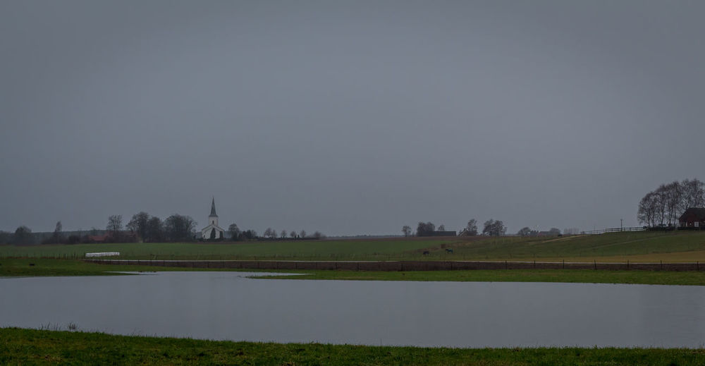 Pond with church in background. Grey December day in the south of Sweden. Church Day Field Grass Landscape No People Outdoors Pond Relaxing Moments Rural Scene Tranquil Scene