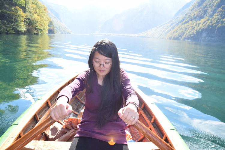 Young woman rowing boat in lake