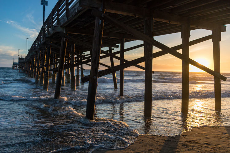 Flowing Water Underneath Architectural Column Outdoors Tranquility Motion Wood - Material Scenics - Nature Wave No People Beauty In Nature Built Structure Nature Horizon Land Pier Horizon Over Water Beach Architecture Sky Sunset Sea Water Newport Beach My Best Photo