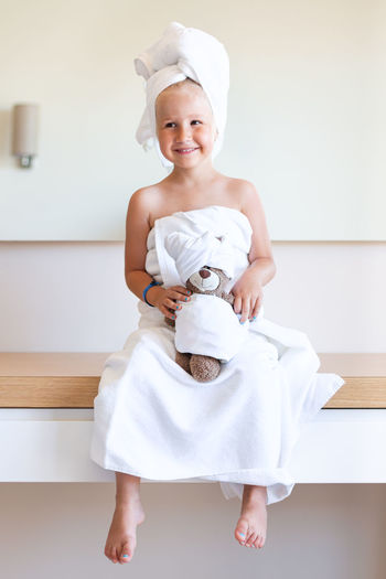 Little girl in a white bath towel and a turban sits, smiles, holds a teddy bear. family look.