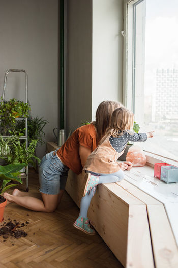 People sitting by window at home