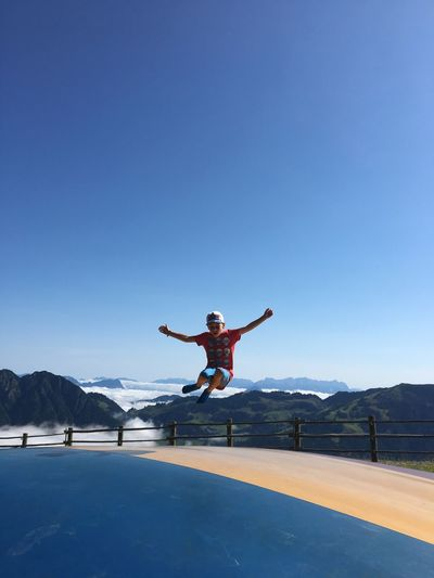 Boy jumping on mountain against clear blue sky