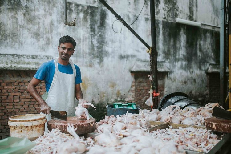 Portrait of butcher cutting meat at market stall