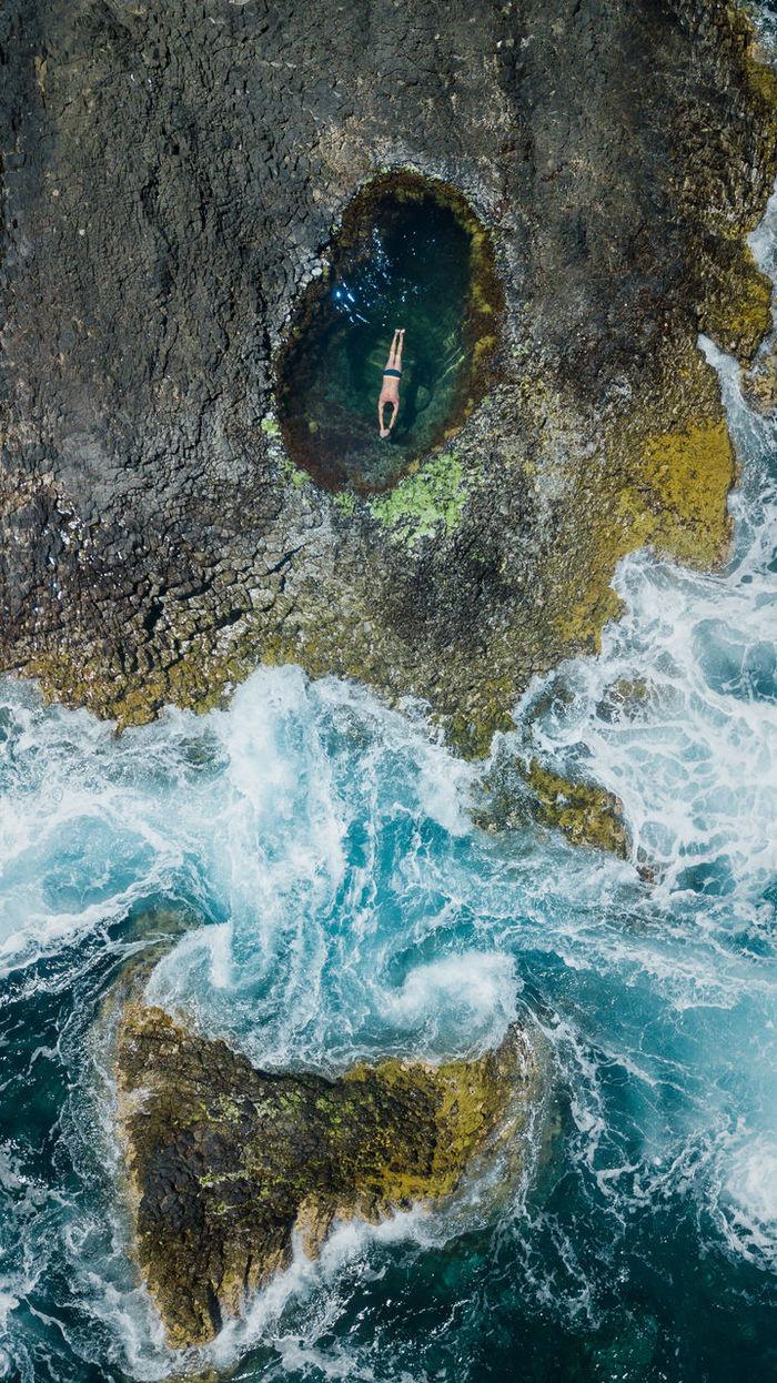 Drone view of man swimming in tidal pool