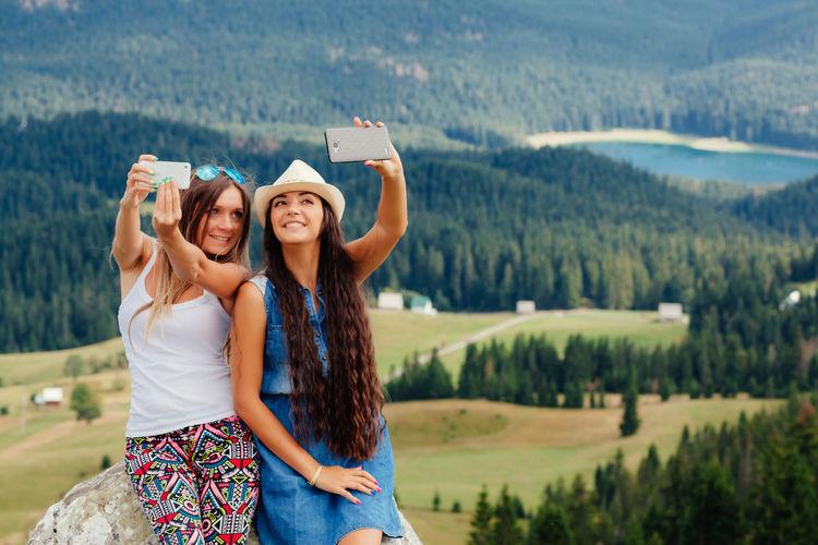 Friends Talking Selfie While Leaning On Rock Against Landscape