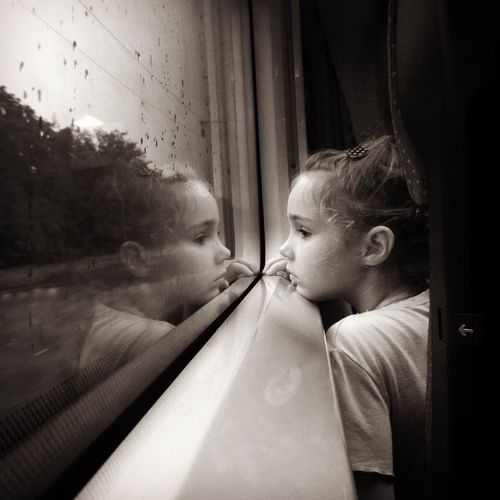 Thoughtful girl looking through window while traveling in train