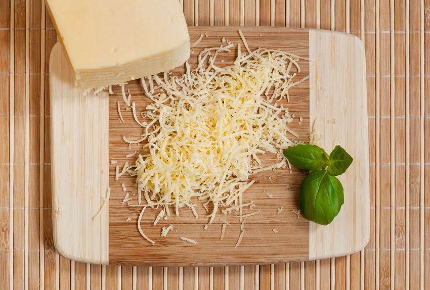 Grated yellow cheese and whole cheese portion lying on bamboo board on mat, green leaf of basil decoration, dairy food in horizontal orientation, nobody, studio shot, view from above. Cheese Chopping Board Food Food And Drink Grate Grated Grated Cheese Grating Grating Cheese No People Piece Shred Shredded Shredded Cheese Shredding Trencher