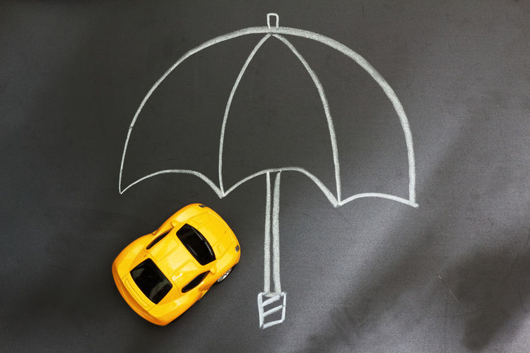 Concept of car insurance and protection Concept Conceptual Umbrella Protection Insurance Claim Damage Lost Security Coverage Financial Death Accident Finance Banking Car Toy Car Yellow Sunlight Blackboard  Chalk Drawing