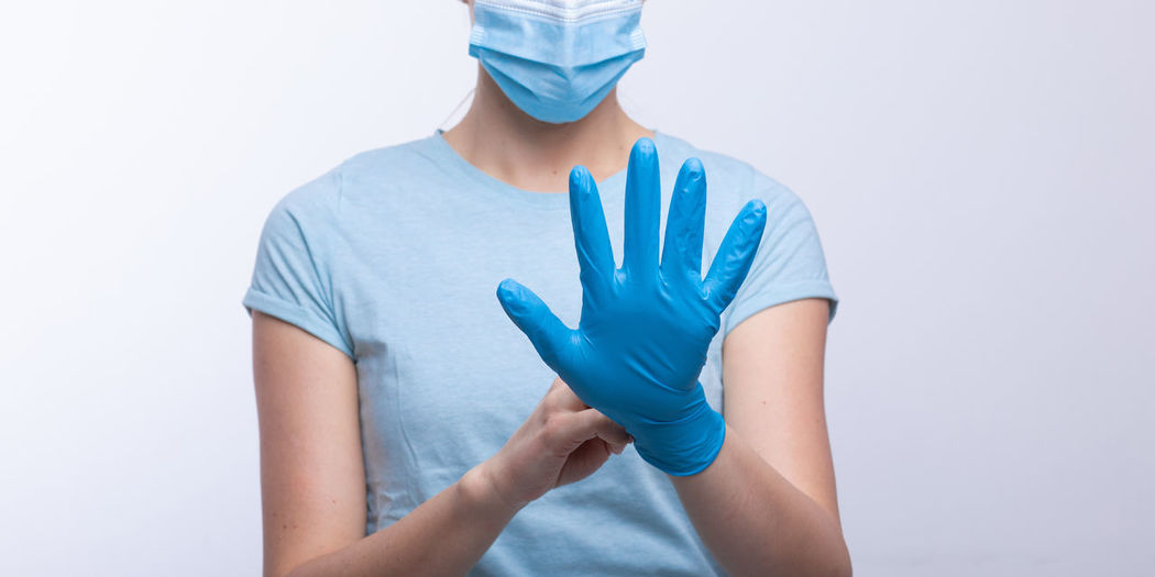 Midsection of doctor in mask wearing surgical glove against gray background