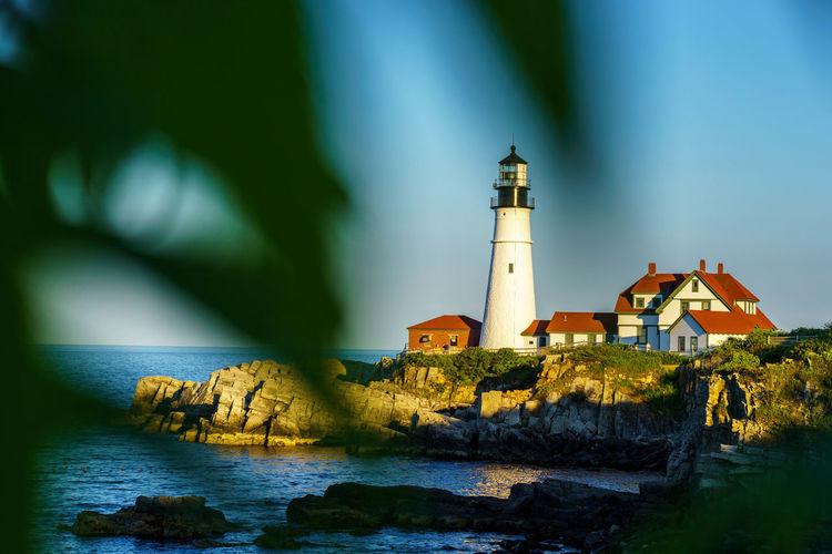 Lighthouse on shore against sky