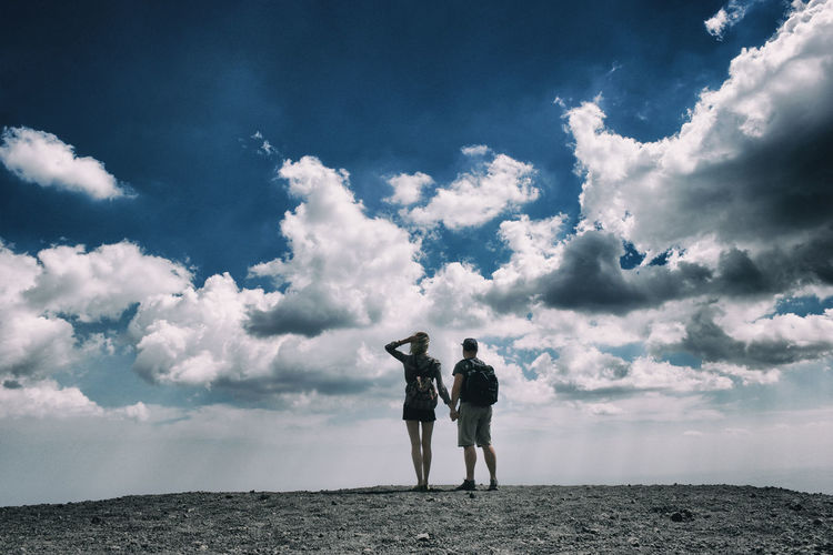 Rear view of couple photographing against sky