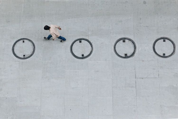 High Angle View Of Man Walking By Manholes On Street