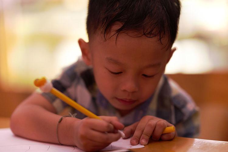 Cute boy writing on paper