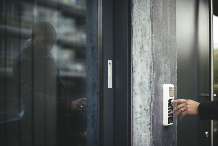 Midsection of person holding glass door