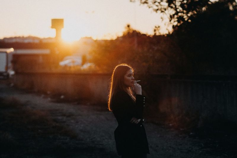 a girl smoking a cigarette Portrait EyeEm EyeEm Best Shots EyeEmNewHere EyeEm Gallery People Young Adult Casual Clothing Lifestyle Outdoors Lifestyles Cigarette  Cigar Smoking Illuminated Tobacco Focus On Foreground EyeEm Selects Texture Nature Teenager Young Women Women Sunset Standing