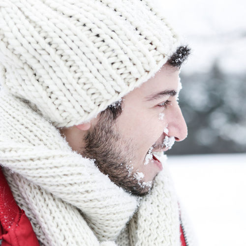 Profile View Of Man Smiling While Looking Away During Winter