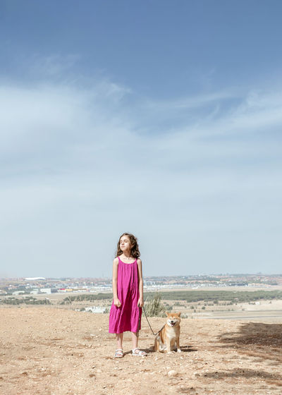 Rear view of girl with dog on beach