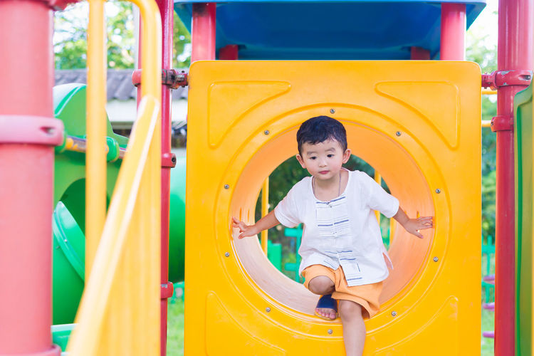 Boy playing on yellow slide in playground