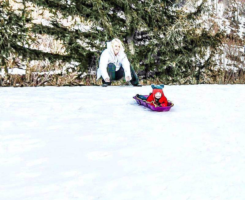 Snow Sports Adventure Outdoor Pursuit Snow Sledding Hill Snowy Hills Pushing Leisure Activity Vacations Outdoors Movement Showing Action Snow Resort Motion Winter Scene Ski Slope Snowy Mountains Snow Skiing Winter Sport Cold Temperature Child Warm Clothing Children Playing Sled Proud