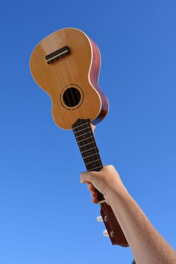 Low angle view of cropped hand holding ukulele against clear blue sky