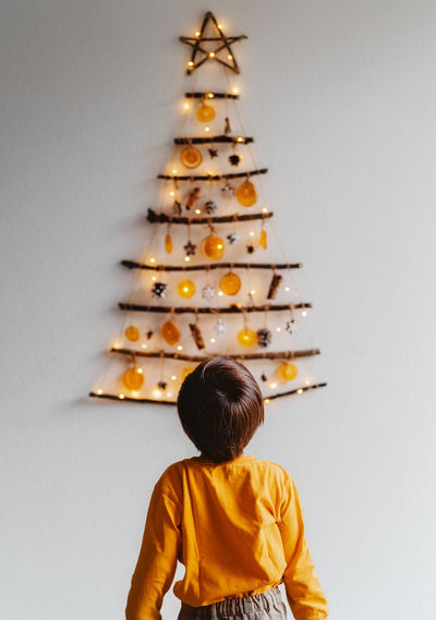 Rear view of child standing in front of handmade craft christmas tree hanging on wall.