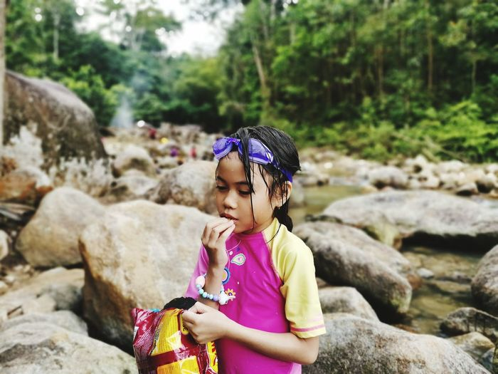 Girl eating food while standing at riverbank in forest
