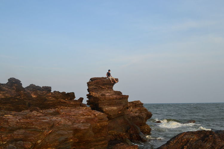 Low angle view of man sitting on cliff by sea against sky