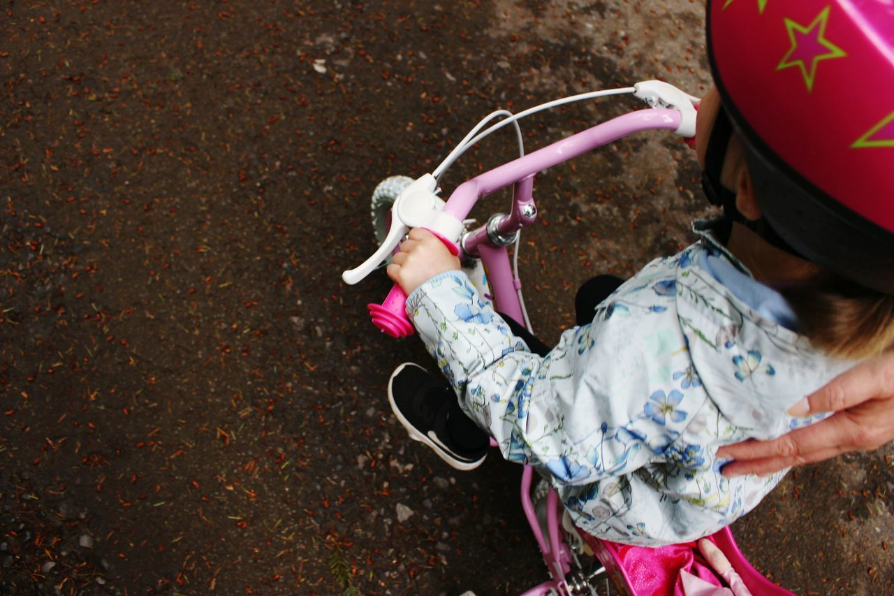 High angle view of girl riding bicycle on street