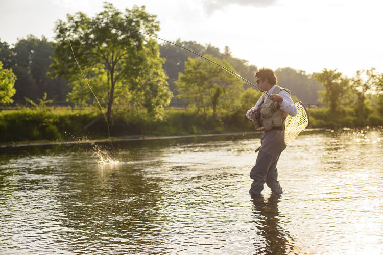 Full length of man fishing in lake against trees