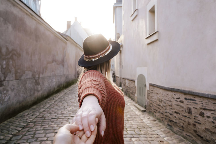 Woman holding hand in alley