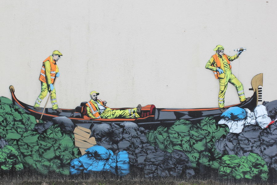 Street Art / Urban Art / Graffiti Art / three men in a small boat / gondola navigating through a pile of garbage bags / painted on a wall in Ostend, Belgium Graffiti Art Boat Day Fluorescent Garbage Gondola - Traditional Boat Graffiti Art Graffiti Wall Men Multi Colored Ostend Outdoors Street Art Streetart