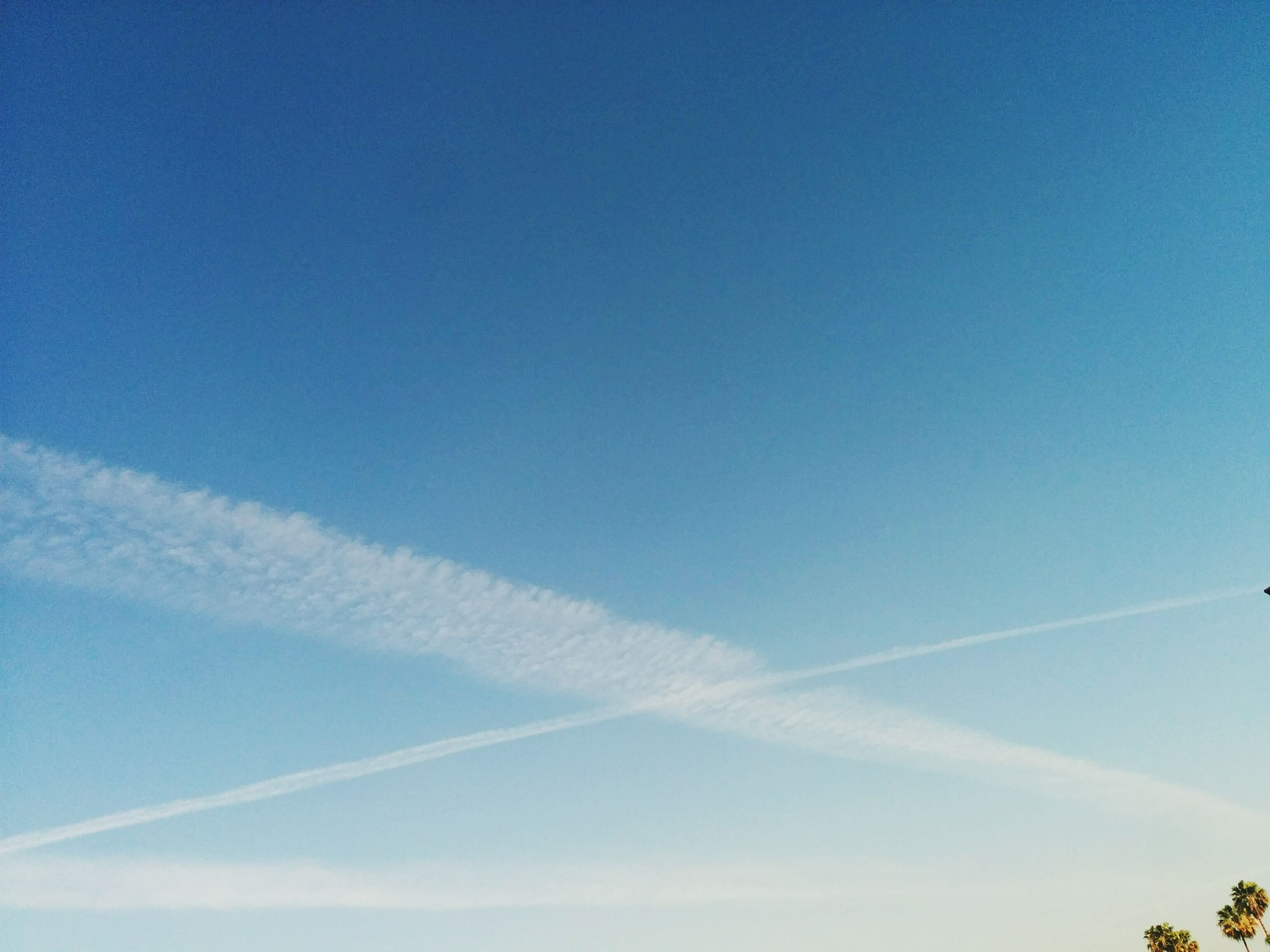 blue, low angle view, vapor trail, sky, copy space, beauty in nature, nature, scenics, tranquility, clear sky, outdoors, day, tranquil scene, no people, cloud - sky, sky only, cloud, high section, idyllic, sunlight