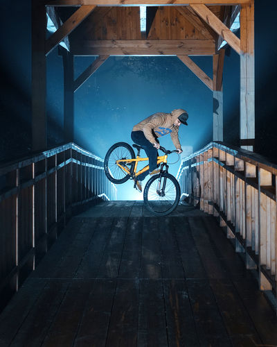 Man cycling on bicycle against wall