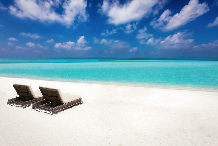 Two sunbeds on a tropical beach; summer holiday concept Maldives Travel Tropics Vacations Beach Caribbean Cloud - Sky Concert Day Horizon Over Water No People Paradise Sand Scenics Sea Sky Sunbed Sunchair Tourism Tranquil Scene Tranquility Travel Destinations Tropical Vacations Water