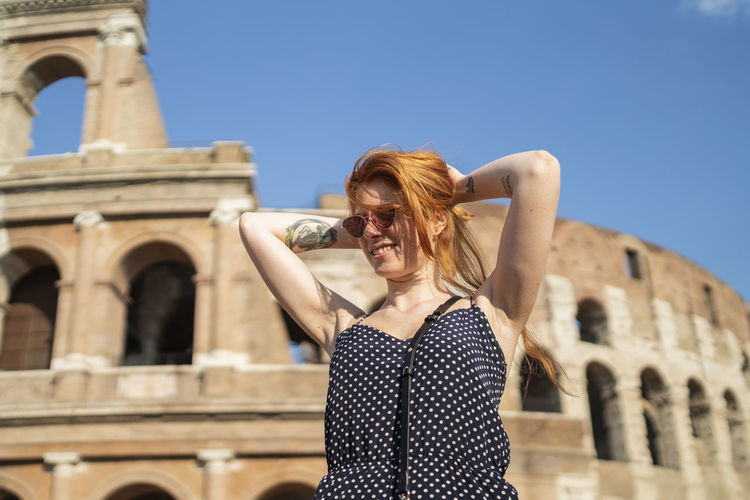 Woman in front of historic building against sky