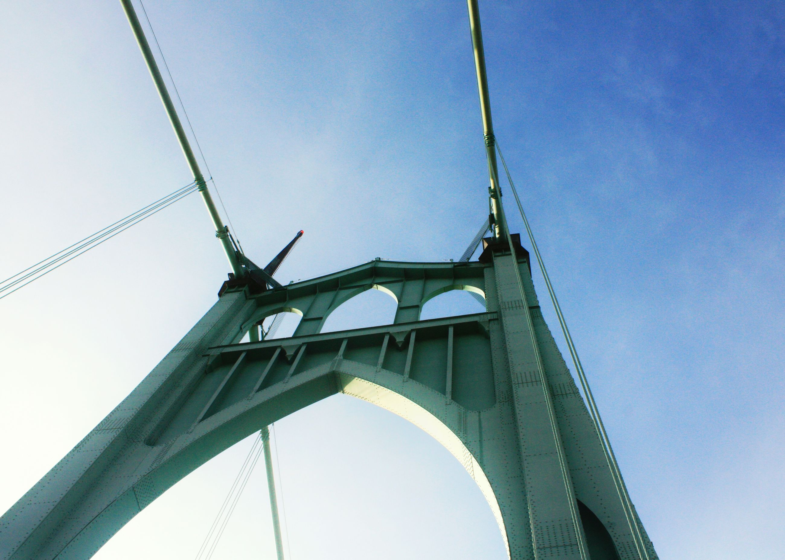 low angle view, connection, built structure, engineering, architecture, clear sky, bridge - man made structure, suspension bridge, sky, blue, metal, transportation, bridge, international landmark, day, famous place, outdoors, travel destinations, no people, tall - high