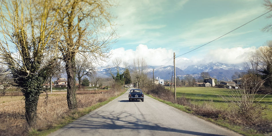 Traveling in countryside road Beauty In Nature Car Cloud - Sky Day Driving Fast Freedom Land Vehicle Nature No People Outdoors Road Road Sign Sky The Way Forward Transportation Traveling Tree